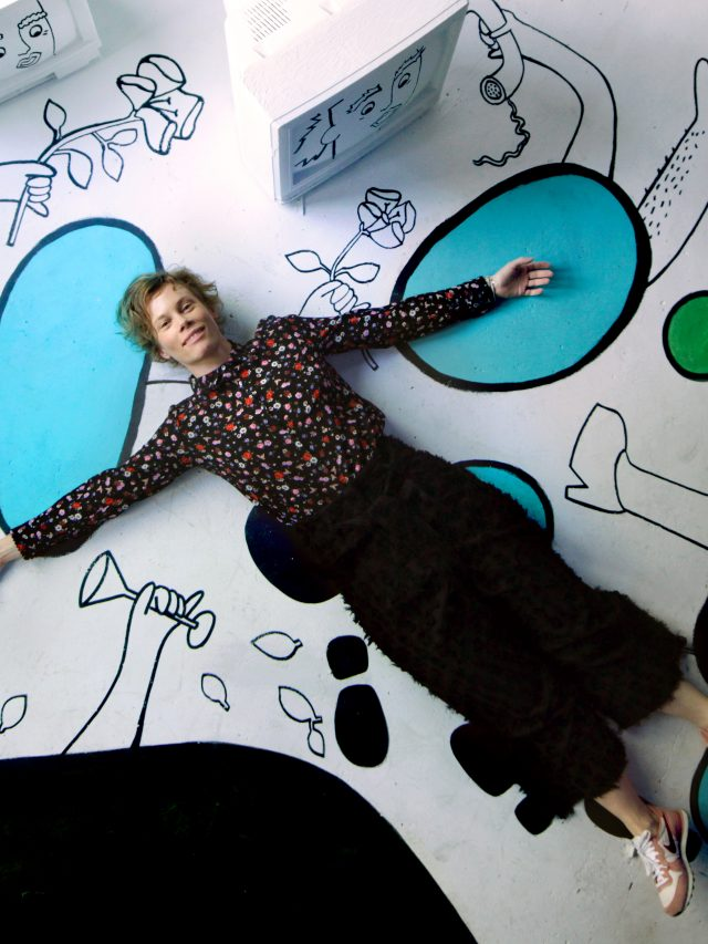 Emma, lying on a floor mural she has painted, looks up at the camera. Her hair is short and her head rests on one of the colorful parts of the artwork, a round blue shape. Her arms stretch out, mirroring the limbs and flowers that are part of the artwork.