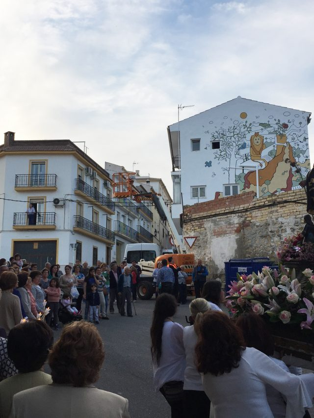 A mural by Emma viewed from the street, where crowds of people have gathered.