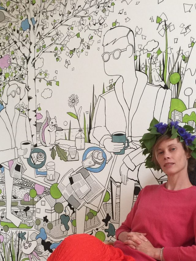 Emma sits in front of mural, wearing a flower crown and a pink/red outfit. Behind her, her artwork shows two people and a squirrel at a table, laid with breakfast food and surrounded by nature.