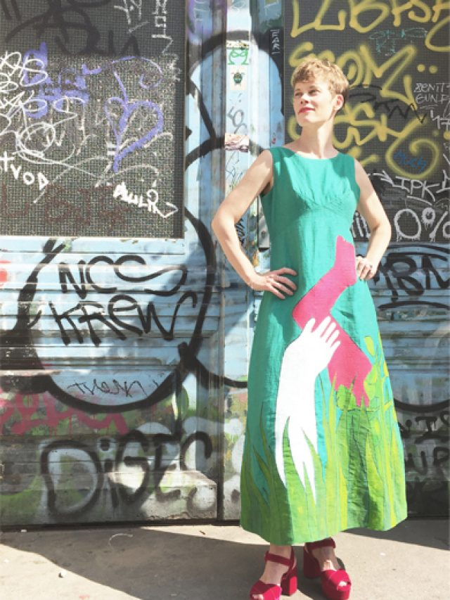 Emma, wearing an aqua dress covered with green foliage resembling flames, and a white arm holding a dark pink limb, stands in front of a heavily graffitied blue door in Berlin.