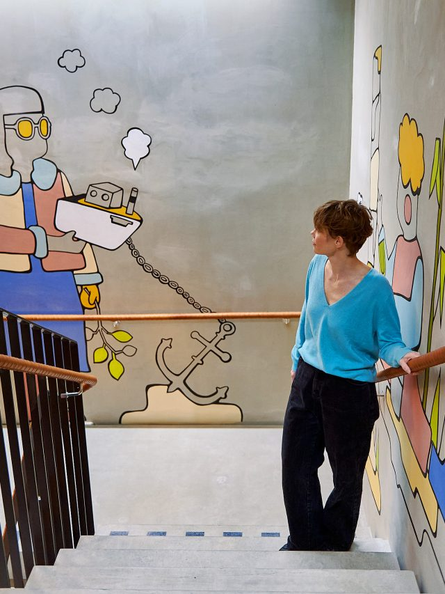 Emma standing on a staircase, beside a mural she has recently painted, covering two walls. She is wearing a blue jumper and her gaze is directed at a figure wearing yellow sunglasses and holding a small boat.